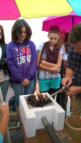 Die Kohle wird entzündet. Sie tut sich schwer dabei - bis aufmerksame Schüler vorschlagen, die Luftzufuhr umzudrehen, also in die Kohle hineinzusaugen und außerdem Sauerstoff aus der Laborflasche dazuzutun. Es klappt!