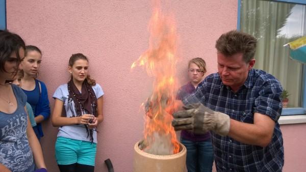 Als die Kohle gut brennt, kommen die Kalkbrocken ins Feuer.
